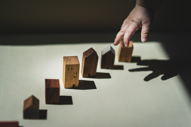 Mãos do bebê que escolhem o mini modelo da casa de madeira. o conceito de relocação, hipoteca