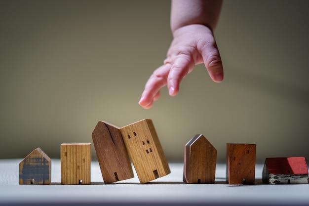 Mãos do bebê que escolhem o mini modelo da casa de madeira.