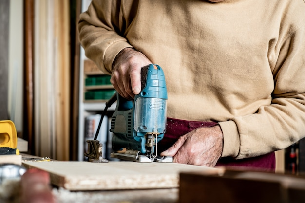 Mãos do carpinteiro com close-up elétrico da serra de vaivém. trabalhar em uma oficina de carpintaria. um homem corta madeira compensada com um quebra-cabeça elétrico. ferramenta elétrica para trabalhar madeira.