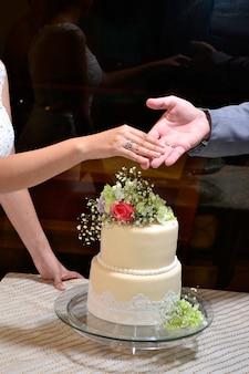 Mãos do casal com o bolo de casamento