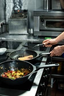 Mãos do chef assando um pedaço de salmão em uma frigideira quente com azeite de oliva enquanto fica perto do fogão elétrico e cozinha peixes e vegetais