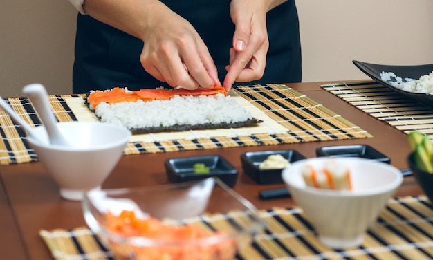 Mãos do chef colocando ingredientes no arroz para fazer sushi