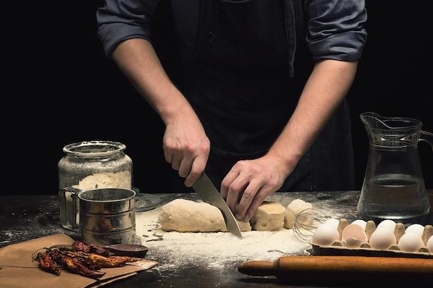 Mãos do chef estão cortando massa de pizza na mesa de madeira