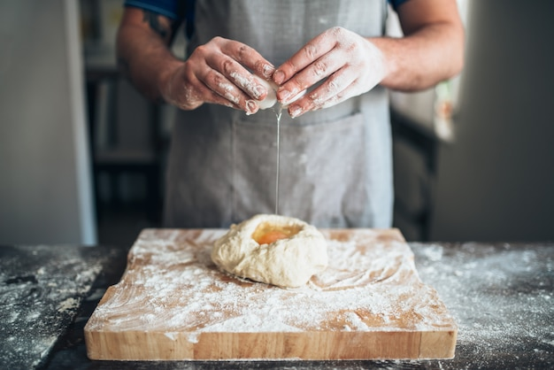 Mãos do chef misturam massa com ovo