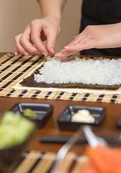Mãos do chef mulher enchendo rolos de sushi japonês com arroz em uma folha de alga nori. foco seletivo em sushi roll.