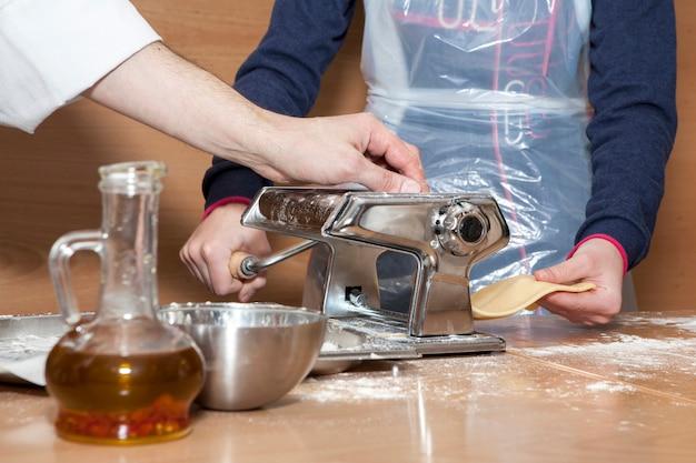Mãos do chef preparando uma porção de fettuccine usando a máquina de macarrão.