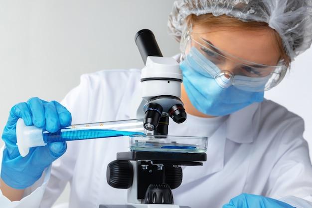 Mãos do cientista fazendo pesquisa química com a ajuda do microscópio