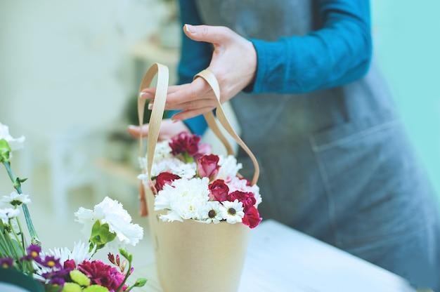 Mãos do close-up da florista com flores. florista que guarda o ramalhete de florescência de tulipas cor-de-rosa em um fundo de linho.
