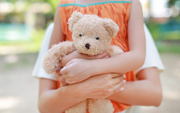 Mãos do close-up da menina da criança pequena e da mamã que abraçam o urso de peluche.