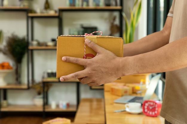Mãos do close up do homem de entrega que guardam o pacote do pacote para entregar.