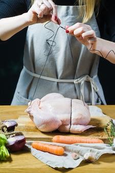 Mãos do cozinheiro chefe que preparam a exploração agrícola de galinha crua.