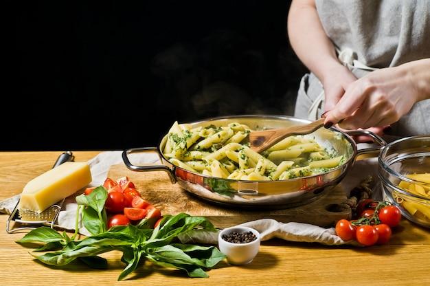 Mãos do cozinheiro chefe que preparam a massa de penne com espinafre.