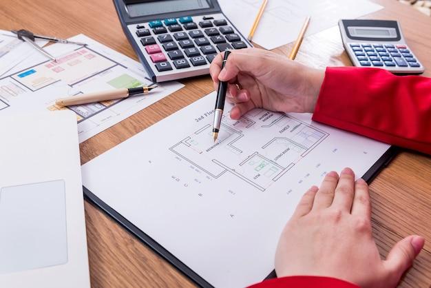 Mãos do designer e planta da casa, desenvolvimento de novo projeto