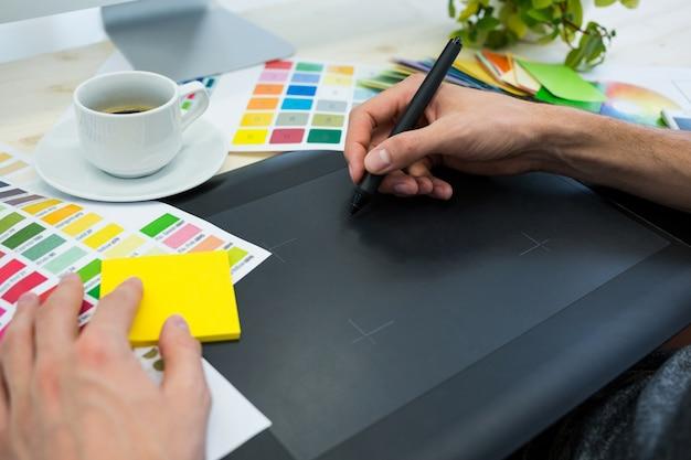 Mãos do designer gráfico do sexo masculino usando gráficos tablet