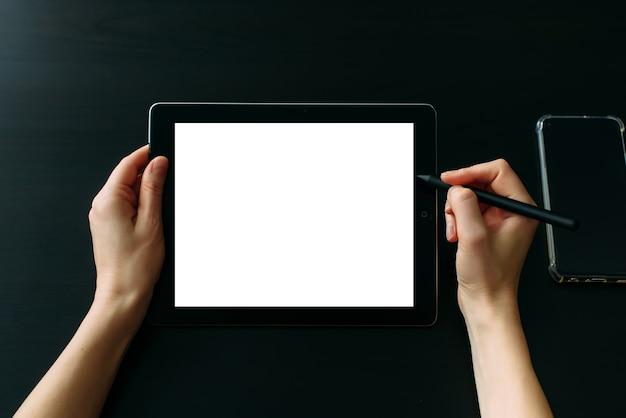 Mãos do designer gráfico trabalhando em tablet com caneta digital, close-up. tela branca vazia, mesa preta.