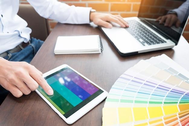Mãos do designer moderno hipster moderno no escritório trabalhando com amostras de cores. homem no local de trabalho escolhendo amostras de cores, closeup. conceito de pessoas criativas.