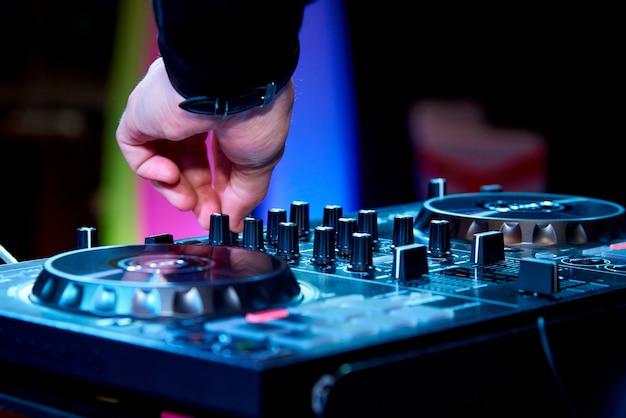 Mãos do dj atrás do painel de controle.