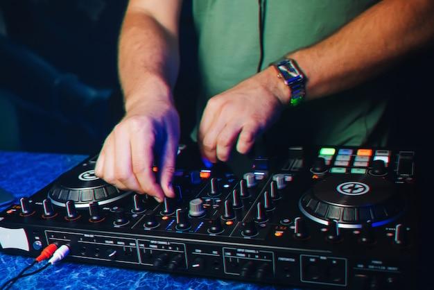 Mãos do dj no mixer
