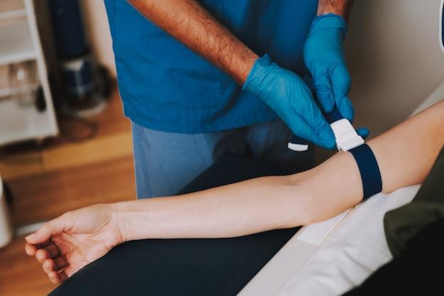 Mãos do doutor consertando a mulher antes de ressonância magnética.
