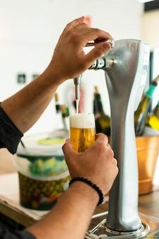 Mãos do empregado de bar na torneira da cerveja que derrama uma cerveja de lager do esboço que serve em um restaurante ou em um bar.