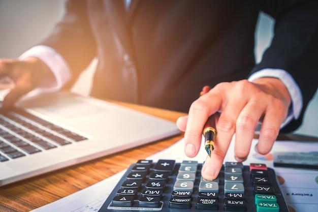 Mãos do empresário com calculadora no escritório e dados financeiros que analisam a contagem na mesa de madeira