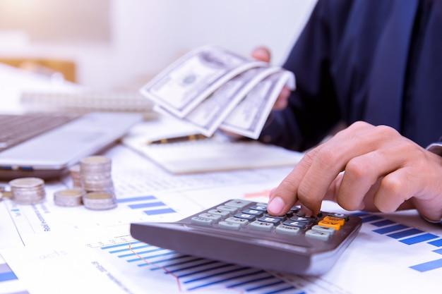 Mãos do empresário com calculadora no escritório e financeira