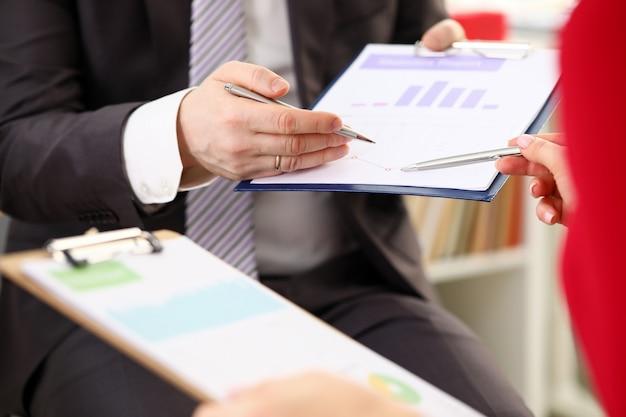 Mãos do empresário discutir relatório financeiro com colega de mulher