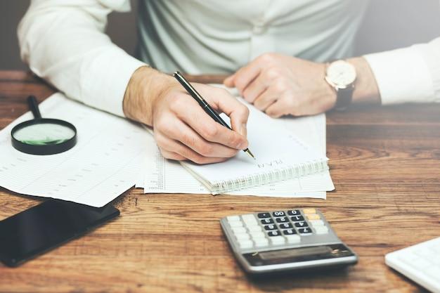 Mãos do empresário, escrevendo uma nota em um bloco de notas