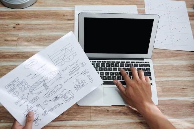 Mãos do empresário verificando o gráfico de ideias gerais e inserindo informações no laptop, vista de cima