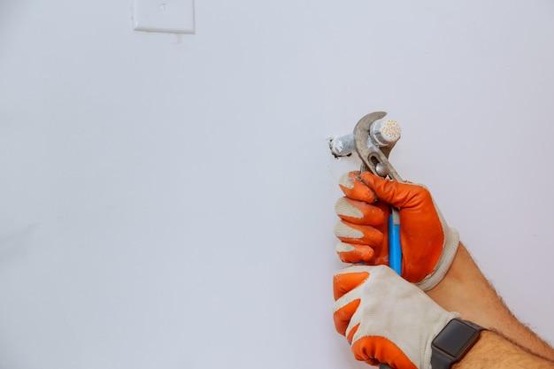 Mãos do encanador usando a chave no encanamento do reparo do trabalho.