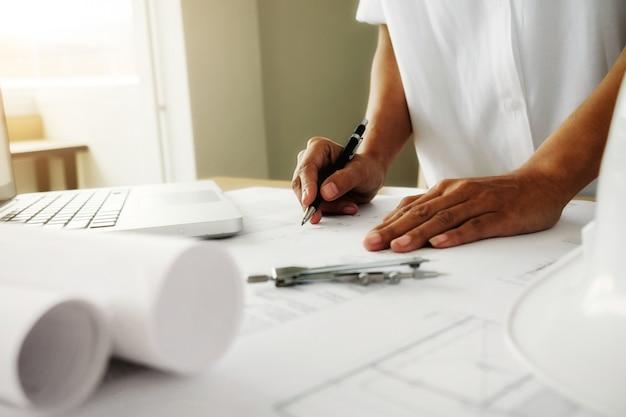 Mãos do engenheiro trabalhando no modelo, conceito de construção. ferramentas de engenharia. tom padrão de filtro retroiluminado, foco suave (foco seletivo)
