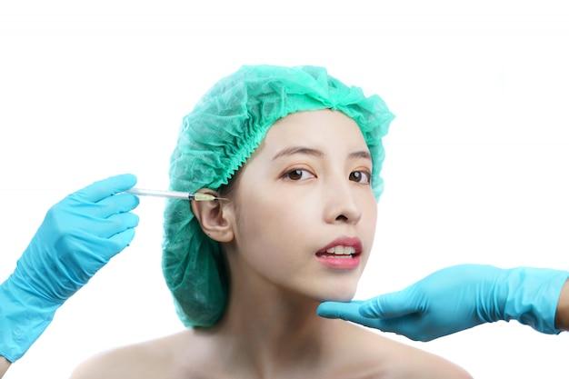Mãos do esteticista que injetam a toxina botulínica a à mulher asiática na área dos olhos.