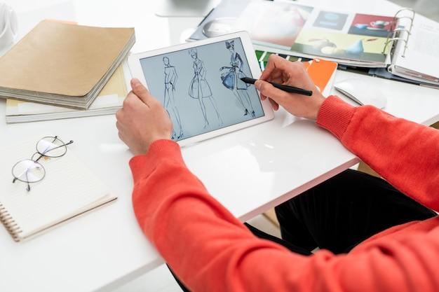 Mãos do estilista criativo com caneta apontando para um dos novos modelos na tela do tablet enquanto está sentado na mesa