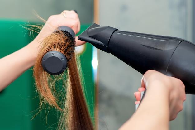 Mãos do estilista secando cabelos castanhos compridos.