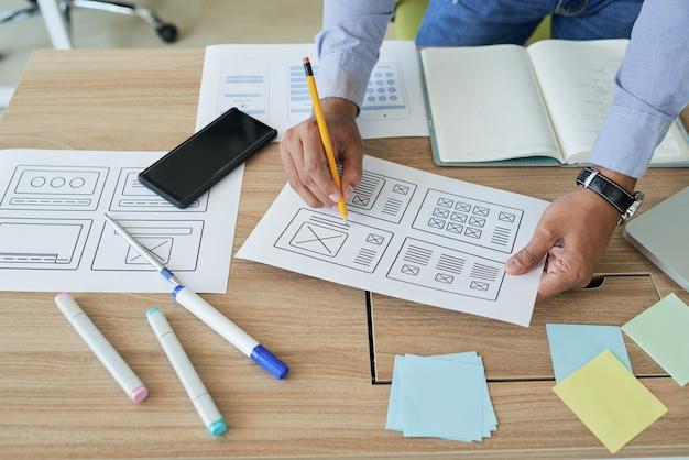 Mãos do gerente de projeto corrigindo documento com layout de interface