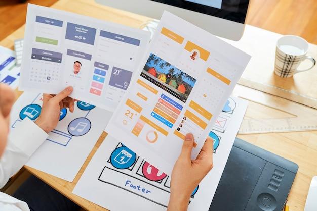 Mãos do gerente de projeto escolhendo entre duas variações de design de aplicativo móvel