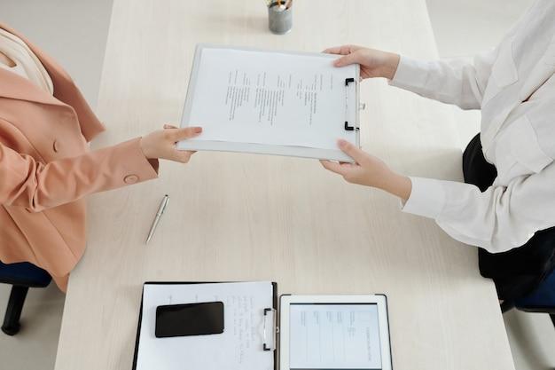 Mãos do gerente de rh pedindo ao candidato para entregar seu currículo impresso, vista de cima