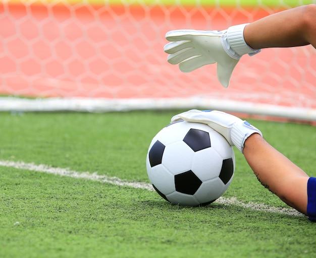 Mãos do goleiro de futebol, pegando a bola, com net