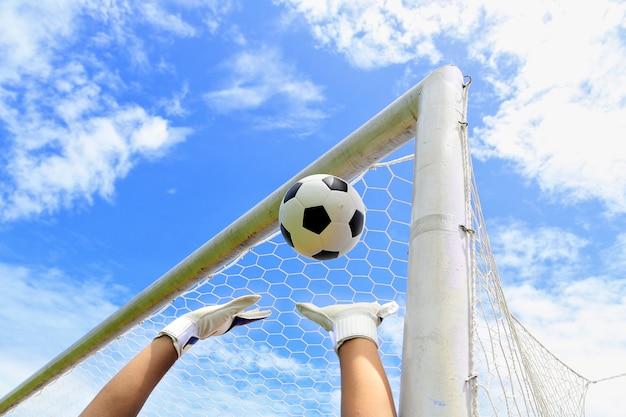 Mãos do goleiro de futebol, pegando a bola