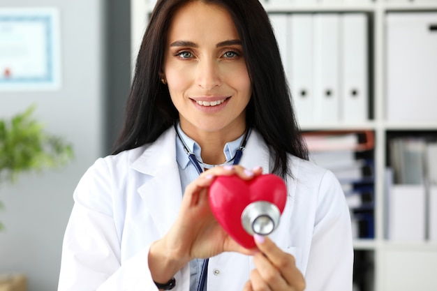 Mãos do gp feminino segurando a cabeça do estetoscópio perto de coração vermelho de brinquedo como profilaxia de problemas cardíacos e retrato de símbolo de recuperação