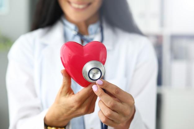 Mãos do gp feminino segurando a cabeça do estetoscópio perto de coração vermelho de brinquedo