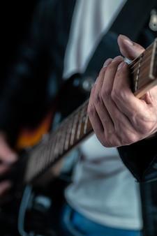 Mãos do guitarrista e cordas da guitarra fechadas