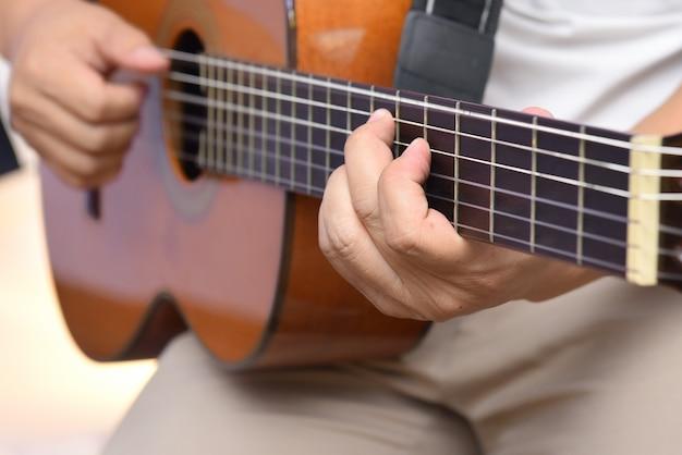 Mãos do guitarrista, tocando uma melodia em um violão de madeira de seis cordas