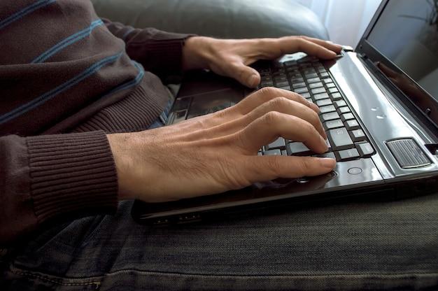 Mãos do homem close-up no teclado do laptop