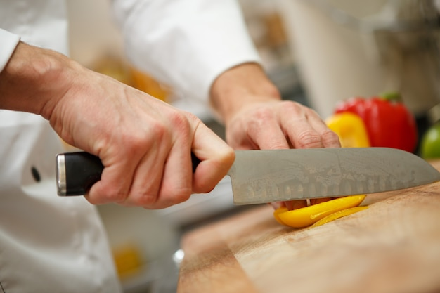 Mãos do homem, corte a pimenta. preparação de salada