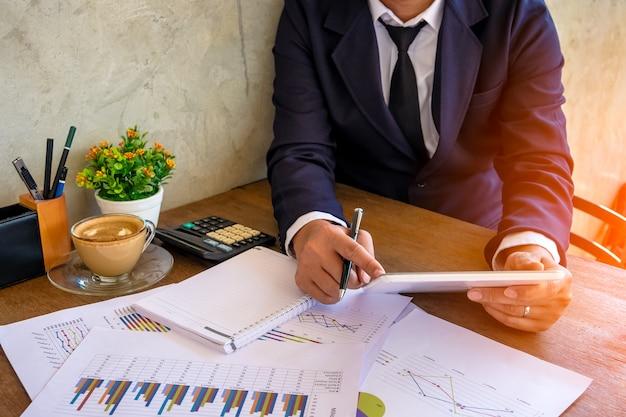 Mãos do homem de negócios em uma mesa com um tablet, um telefone e uma xícara de café em um escritório