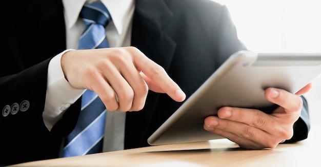 Mãos do homem de negócios usando a tabuleta e a tecnologia, trabalho em linha.
