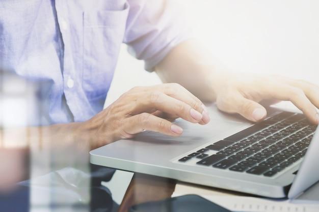 Mãos do homem digitando no teclado do laptop.