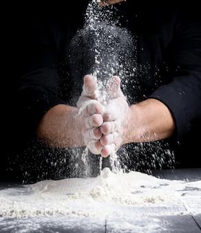Mãos do homem e respingo de farinha de trigo branca