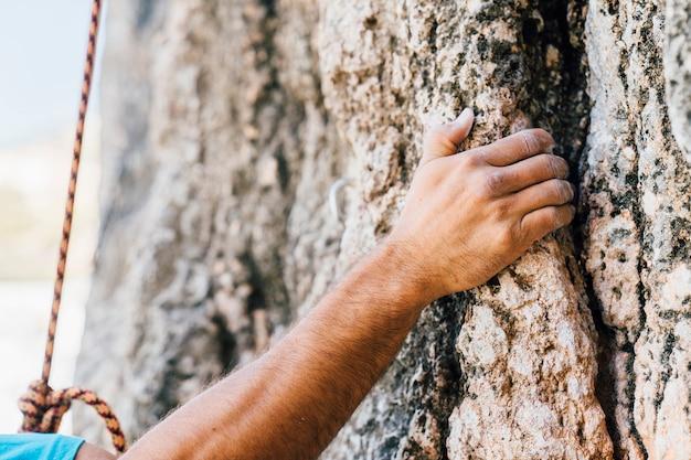 Mãos do homem escalando